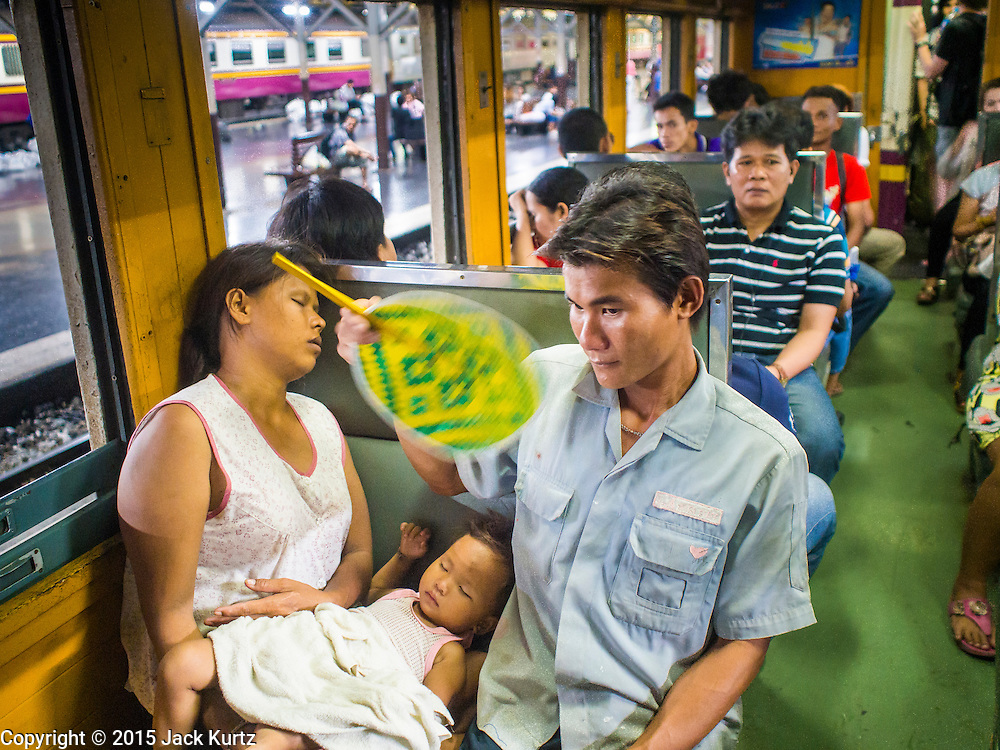 11 APRIL 2015 - BANGKOK, THAILAND:  People on a 3rd class train going to Aranyaprathet on the Cambodian border wait for the train to pull out of Hua Lamphong train station in Bangkok. More than 130,000 passengers streamed through Bangkok's main train station Friday ahead of Songkran, Thailand's traditional new year celebration. Songkran will be celebrated April 13-15 but people started streaming out of Bangkok on April 10 to go back to their home provinces.   PHOTO BY JACK KURTZ