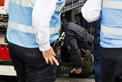 London, UK. 6 September, 2019. Metropolitan Police officers remove an activist who had locked herself beneath a truck making a delivery to ExCel London for DSEI, the world's largest arms fair. The road remained blocked for several hours. The fifth day of protests against the arms fair was themed as Stop The Arms Fair: Stop Climate Change in order to highlight links between the fossil fuel and arms industries.