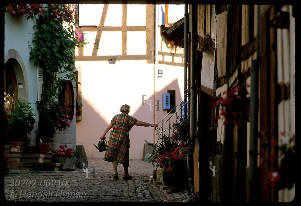 Elderly woman heads inside after watering her flower boxes along cobblestone street; Eguisheim. France