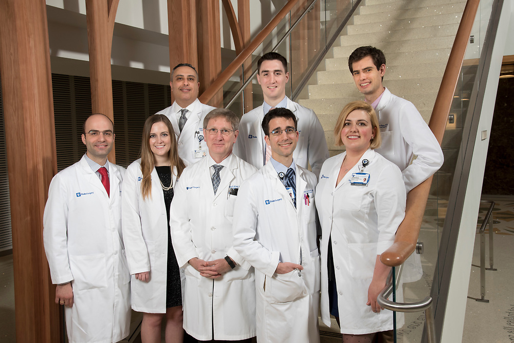 interns in the Department of General Surgery pose with Dr. Kirk in the atrium of the Duke Cancer Center