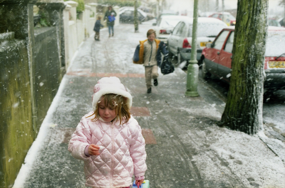 A small girl walking home from school eats snow.