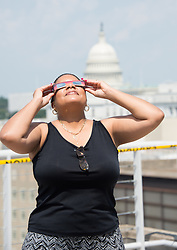 NASA employee Denise Young uses protective glasses to view a partial solar eclipse from NASA Headquarters rooftop Monday, Aug. 21, 2017 in Washington,DC. A total solar eclipse swept across a narrow portion of the contiguous United States from Lincoln Beach, Oregon to Charleston, South Carolina. A partial solar eclipse was visible across the entire North American continent along with parts of South America, Africa, and Europe.  Photo Credit: (NASA/Connie Moore)