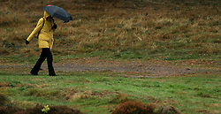 A spectator shelters from the bad weather during day four of the British Masters at Walton Heath Golf Club, Surrey.