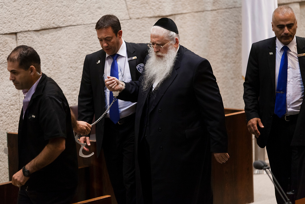 Knesset Member Rabbi Meir Porush of the Ashkenazi ultra-Orthodox United Torah Judaism Party is being escorted by Knesset security staff after handcuffing himself to the Knesset podium, during the first reading of a bill that would significantly increase the enlistment of ultra-Orthodox Israelis in the Israel Defense Forces and national service, at the Israeli parliament in Jerusalem, on July 23, 2013.