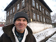 Nowosibirsk/Russische Foederation, RUS, 19.11.07: Passant vor einem traditionellen Holzhaus in der sibirischen Hauptstadt Nowosibirsk. <br /> <br /> Novosibirsk/Russian Federation, RUS, 19.11.07: Passerby in front of a traditional wooden house  in Novosibirsk - the capital city of Siberia .