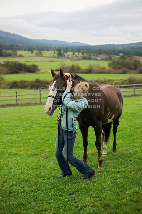 Image of a girl farmer leading her horse to the barn at the end of the day, San Juan Island, model and property released by Randy Wells