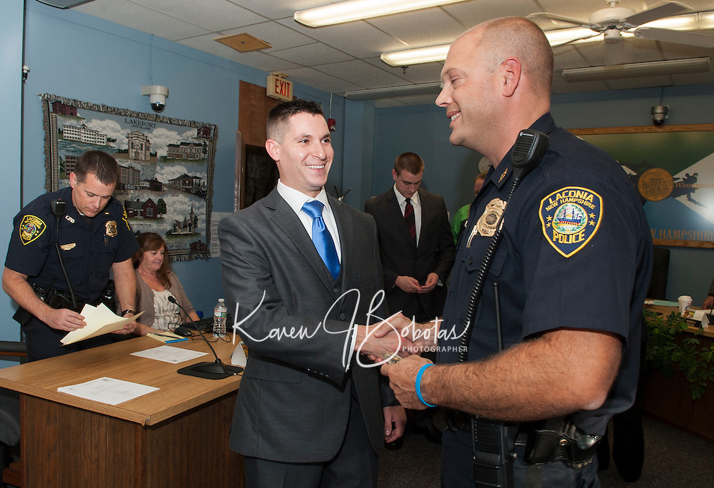 Police Officer Joseph Turner shakes hands with Chief Chris Adams just after the swearing in ceremony at Laconia City Hall Thursday afternoon.  (Karen Bobotas/for the Laconia Daily Sun)