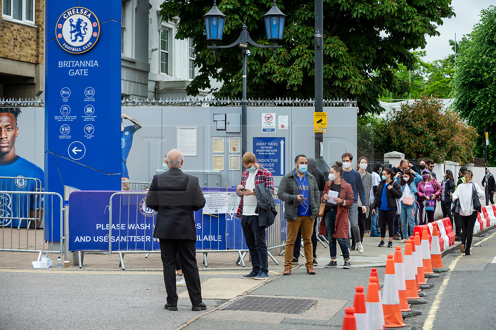 © Licensed to London News Pictures. 19/06/2021. LONDON, UK.  People queue up to receive a Pfizer vaccine jab at a mass vaccination centre at Stamford Bridge, the home of Chelsea FC, as the capital aims for 100,000 doses administered per day.  West Ham, Charlton and Tottenham Hotspur are other London football clubs offering walk-ins. With cases of the Delta variant increasing, the UK government has invited all over 18s for a Covid-19 vaccination in an effort to have as many people to be vaccinated by July 19th, the revised date when all lockdown restrictions are relaxed.  Photo credit: Stephen Chung/LNP