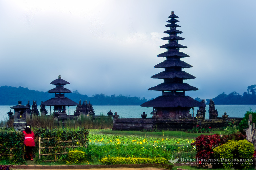 Bali, Tabanan, Bratan. The Ulun Danu temple is beautifully situated at the banks of Lake Bratan. A woman brings offerings.