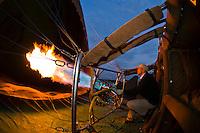 Balloon pilot J. P. Lemaire of Transworld Safaris inflates a balloon for a sunrise flight over Masai Mara National Reserve, Kenya