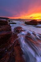 Dramatic sunrise and crashing waves along the Atlantic Coast in Acadia National Park, Maine, USA
