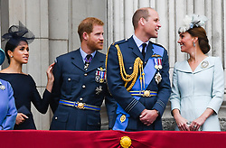 Meghan, Duchess of Sussex, Prince Harry, Duke of Sussex, Prince William, Duke of Cambridge and Catherine, Duchess of Cambridge stand on the balcony of Buckingham Palace in London to watch the flypast to mark the centenary of the RAF (Royal Air Force)  on July 10, 2018.
