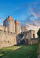 Carcassonne medieval historic gate fortifications and battlement walls, Carcassonne France . The medieval citadel of Carcassonne, known as the Cité de Carcassonne, is a medieval fortress dating back to the Gallo-Roman period and restored by the theorist and architect Eugène Viollet-le-Duc in 1853. It was added to the UNESCO list of World Heritage Sites in 1997. The fortified city of Carcassonne consists essentially of a concentric design of two outer walls with 53 towers and barbicans to prevent attack by siege engines. Carcassonne  castle itself possesses its own drawbridge and ditch leading to a central keep. The walls of Carcassonne consist of towers built over quite a long period. One section is Roman and is notably different from the medieval walls.<br /> <br /> <br /> Visit our MEDIEVAL PHOTO COLLECTIONS for more   photos  to download or buy as prints https://funkystock.photoshelter.com/gallery-collection/Medieval-Middle-Ages-Historic-Places-Arcaeological-Sites-Pictures-Images-of/C0000B5ZA54_WD0s