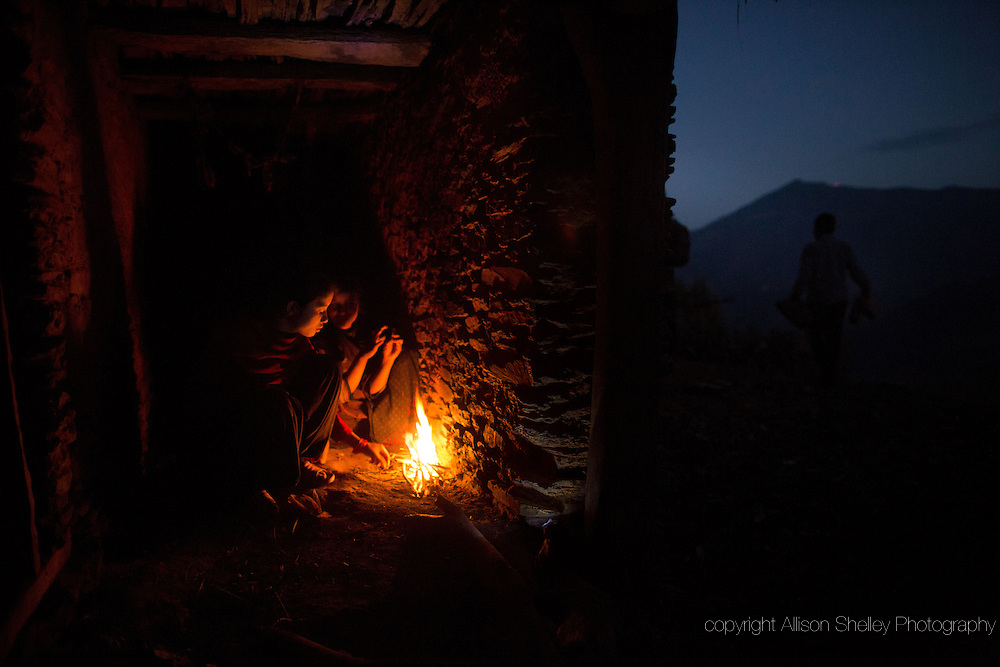 Nabina, 17, left, and Khadi, 12, huddle around a fire for warmth as they prepare to sleep in the household chaupadi shelter, a crawlspace with no door under the home shared with the family's animals, where the women of the household sleep during their periods, in Rima village, Achham, Nepal.