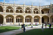 Tourists view stone pillars and cloisters of famous Monastery of Jeronimos - Mosteiro  dos Jeronimos in Lisbon, Portugal