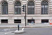 A contractor workman kneels on the ground to maintain the paintwork of a building near Parliament Square in Westminster, on 14th October, 2021, in Westminster, London, England.