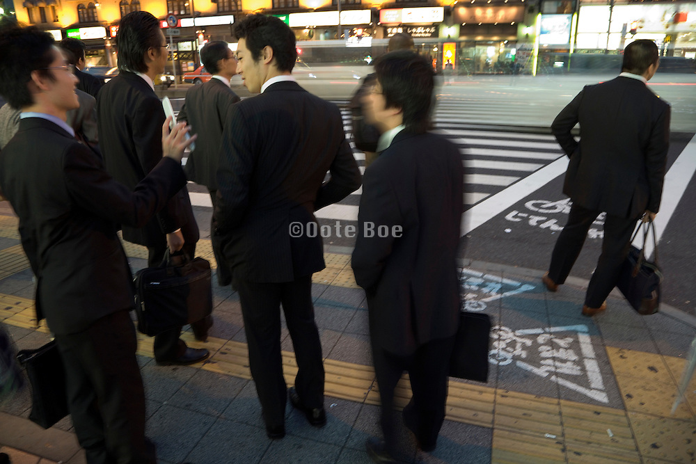 young businesspeople meeting up after work at a zebra crossing Japan Tokyo