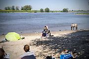 Nederland, Nijmegen, 6-5-2018Warme zomerse dag op het Waalstrand van Nijmegen in de Ooijpolder, makkelijk te bereiken via de voetgangersbrug Ooijblik die hier ligt. Het zwemmen in de rivier de waal, rijn, is gevaarlijk vanwege de veraderlijke stroming en de drukke scheepvaart. Veel mensen maken een wandeling door de ooijpolder . Wilde paarden, koniks, lopen langs het water . De paarden zijn nieuwsgierig naar her eten en voedsel wat de mensen bij zich hebben. Er is een kleine nevengeul gegraven met een voetgangersbruggetje eroverheen zodat het gebied nog meer natuurwaarde heeft gekregen .Foto: Flip Franssen