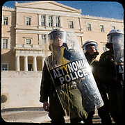 Riot Police in front of the Greek parliament. <br /> <br /> Following the murder of a 15 year old boy, Alexandros Grigoropoulos, by a policeman on 6 December 2008 widespread riots, protests and unrest followed lasting for several weeks and spreading beyond the capital and even overseas<br /> <br /> When I walked in the streets of my town the day after the riots I instantly forgot the image I had about Athens, that of a bustling, peaceful, energetic metropolis and in my mind came the old photographs from WWII, the civil war and the students uprising against the dictatorship. <br /> <br /> Thus I decided not to turn my digital camera straight to the destroyed buildings but to photograph through an old camera that worked as a filter, a barrier between me and the city.
