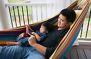 The father and son sit in a hammock and use a tablet.