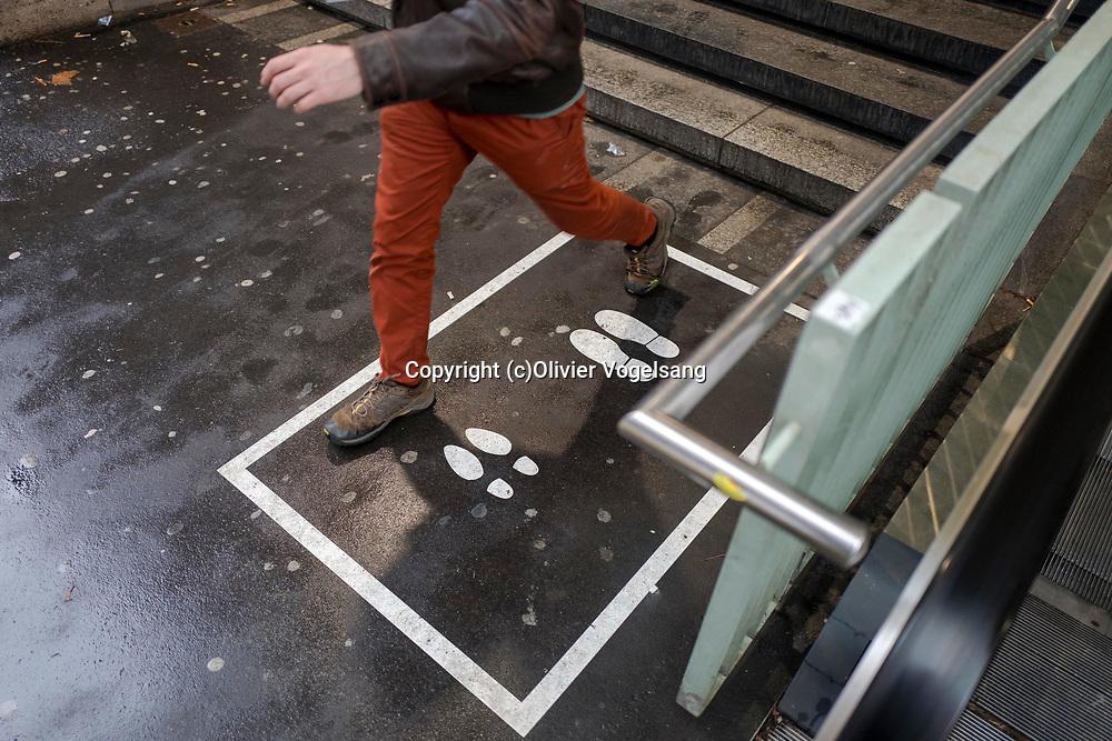 Lausanne, Janvier 2018. Un marquage au sol avec des traces de pieds en descendant sous-gare de Lausanne. Un lieu autorisé par les CFF pour la récolte de signature. © Olivier Vogelsang