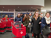 """28 NOVEMBER 2019 - ANKENY, IOWA: Shoppers rush into the Target store in Ankeny, Iowa, just after it opened. """"Black Friday"""" is the unofficial start of the Christmas holiday shopping season and has traditionally thought to be one of the busiest shopping days of the year. Brick and mortar retailers, like Target, are facing increased pressure from online retailers this year. Many retailers have started opening on Thanksgiving Day. Target stores across the country opened at 5PM on Thanksgiving to attract shoppers with early """"Black Friday"""" specials.     PHOTO BY JACK KURTZ"""