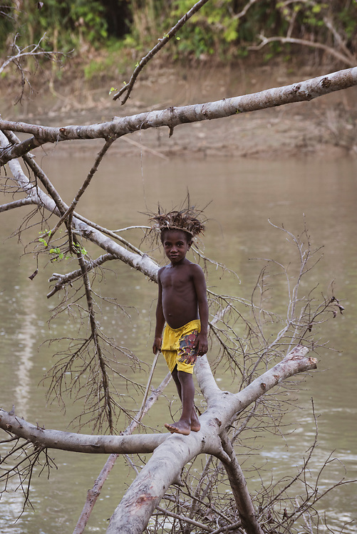 A boy walks across a fallen tree in the village of Yar, located on the Keram River in the East Sepik Province of Papua New Guinea.<br /> <br /> (June 21, 2019)
