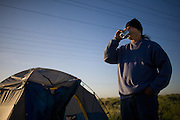 A homeless man drinks a beer at daybreak before having to move camp in Sacramento, CA.