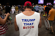 A supporter of Republican presidential candidate Donald Trump wears a shirt referencing Democratic presidential candidate Hillary Clinton at a campaign rally at the Tampa Convention Center in Tampa, Florida, June 11, 2016.