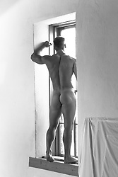 nude body builder at home in a large window