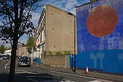 Giant circle painted on the side wall of a Victorian terraced home in a south London street.