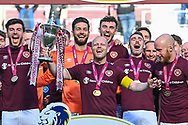 The Hearts players celebrate as Steven Naismith (centre) lifts the SPFL Championship trophy after the final whistle of the SPFL Championship match between Heart of Midlothian and Inverness CT at Tynecastle Park, Edinburgh Scotland on 24 April 2021.
