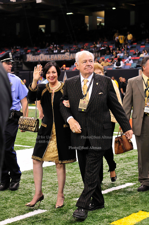 """World Champion New Orleans Saints owner Tom Benson struts on the field sporting a one of a kind hand made """"special """"pinstripe suit"""" The striping says """" New Orleans Saints World Champions"""" all over the  Black & Gold Suit!!! His wife Gayle , on his arm,had it made for him as a surpirse and he was presented it right before opening of the NFL season in New Orleans Louisiana Thurs Sept. 9,2010. The Saints beat the Minnessota Viking 14-9. Phot © Suzi Altman"""