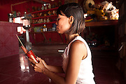 Apr. 3, 2010 - KHUN SAMUTCHINE, THAILAND: A Thai woman shakes fortune telling sticks in a Chinese shrine in Khun Samutchine. The Chinese shrine was moved and rebuilt in the new village when sea water overtook the old one, but the Buddhist temple is now 2 kilometers away and completely surrounded by sea water. Rising sea levels brought about by global climate change threaten the future of Khun Samutchine, a tiny fishing village about 90 minutes from Bangkok on the Gulf of Siam. The coastline advances inland here by about 20 metres (65 feet) per year causing families to move and threatening the viability of the village. The only structure in the village that hasn't moved, their Buddhist temple, is completely surrounded by water and more than 2 kilometers from the village. The temple and the village have asked the Thai government and several NGOs for help, but the only help so far is a narrow concrete causeway the government is building that will allow people to walk into the temple from a boat landing two miles away. The walk to the village from a closer boat landing is shorter, but over an unimproved mud flat that is nearly impassible in the rainy season.  PHOTO BY JACK KURTZ