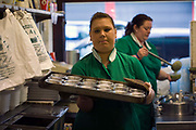 Sharon takes empty pie cases back to to kitchens at Manze's Eel, Pie and Mash shop on Tower Bridge Road London, UKEel, pie and mash shops are a traditional but dying business. Changing tastes and the scarcity of the eel has meant that the number of shops selling this traditional working class food has declined to just a handful mostly in east London. The shops were originally owned by one or two families with the earliest recorded, Manze's on Tower Bridge Road being the oldest surviving dating from 1908. Generally eels are sold cold and jellied and the meat pie and mash potato covered in a green sauce called liquor.