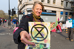 A woman hands out leaflets as hundreds of environmental protesters from Extinction Rebellion occupy Marble Arch, camping in the square and even on the streets, blocking access to traffic on Park Lane and Oxford Street in London's usually traffic-heavy west end. . London, April 16 2019.
