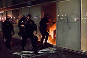 NOVEMBER 9, 2016 - OAKLAND, CA: California Highway Patrol officers survey a fire started by a group of Anti-Trump protesters in the CBRE offices in the Oakland Federal Building, in Oakland, California on November 9, 2016. (Photo by Philip Pacheco)