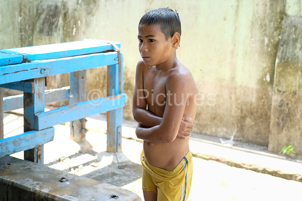 A boy shivering at a small indoor swimming pool in Insein, a suburb of Yangon on 17th May 2016 in Myanmar
