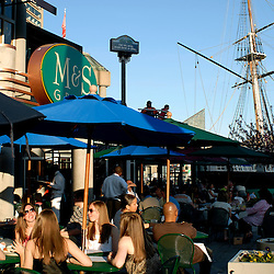 Weekend revelers enjoy the sun and food outside on the patio of one of many restaurants on the waterfront of Baltimore's Inner Harbor.  A tall ship can be seen docked in the background...Photo by Susana Raab