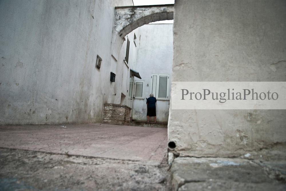 Siamo in puglia, a Specchia cittadina della provincia di Lecce, situato a circa 60 Km a sud del capoluogo di provincia..Si presenta come un paese traquillo ma vivo..Le strade luminose e tranquille sono pulite, e presentano una pavimentazione a lastroni antichi..Il centro storico è un' intera area pedonale ed è spesso scenario di manifestazioni sacre e culturali..La gente è gentile ed ospitale e si è lasciata fotografare con tranquillità, facendosi riprendere nel loro fare quotidiano, quasi fosse abituata ad essere fotografata..Quest'area del salento è meta di un turismo alla ricerca della tranquillità e della cultura intesa anche come enogastronomia, e soprattutto di un aria sana, pulita, molto diversa dalla solita respirata in città e molto spesso in grandi città del nord...La piazza e le strade nei dintorni sono animate dalla popolazione, che approfitta del primo fresco del pomeriggio per uscire a stare in compagnia..Gente del posto, anziani in prima linea vivono la piazza, ragazzi passeggiano e visitano il palazzo e le attività commerciali..Passeggini e biciclette percorrono le strette vie del borgo, qua e là la gente fa capolino e si appresta a uscire a ritirare i panni o a far visita al vicino.