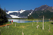 Guests search for black bears and enjoy the scenery from the boardwalk of Kenai Fjords Glacier Lodge on the Lower Pedersen Lagoon.