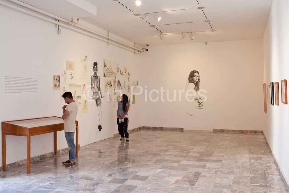 Visitors look at the artworks on show at the Museo de los Pintores Oaxaqueños / Museum of Oaxacan painters. Oaxaca is known throughout Mexico and internationally for its cultural and artistic heritage and is still home to many important contemporary artists and performers.