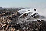 New Delhi, India - <br /> <br /> Garbage Mountain<br /> <br /> Just a few miles from the famous Akshardham temple, where tourists flock to see the structure's sandstone and marble work, the 29-hectare, slum-surrounded Ghazipur landfill in east Delhi seems a world apart. Each day hundreds of mainly migrant workers earn a meager living at the landfill by collecting recyclable material like plastic, metal and even hair to sell. The dump is the last port of call for Delhi's trash, having already been picked through by other waste collectors who collect bags of garbage directly from homes. Delhi is home to three landfills where around 6,000 tons of trash is dumped daily. Studies have shown that living near a landfill increases the risk of cancer, birth defects and asthma.<br /> <br /> Photo shows: Amidst a thick blanket of smoke, a rag picker sifts through a pile of rubbish to pick out pieces of glass, metal and plastic at the Ghazipur landfill. <br /> ©Chinky Shukla/Exclusivepix Media