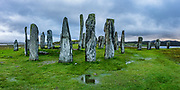 """Erected 4600 years ago, the Callanish Standing Stones are one of the most spectacular megalithic monuments in Scotland. The main site known as """"Callanish I"""" forms a cross with a central stone circle erected circa 2900-2600 BC. More lines of stones were added by 2000 BC (the close of the Neolithic era), and it become a focus for rituals during the Bronze Age. From 1500-1000 BC, farmers emptied the burials and ploughed the area. After from 800 BC, peat accumulated 1.5 meters deep and buried the stones until removed in 1857. Visit this spectacular ancient site near the village of Callanish (Gaelic: Calanais), on the Isle of Lewis, Outer Hebrides (Western Isles), Scotland, United Kingdom, Europe. This image was stitched from several overlapping photos."""