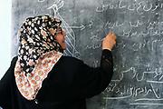 Afghanistan. Mazar-e-Sharif high school. Middle-aged teacher writing on blackboard in Dari.