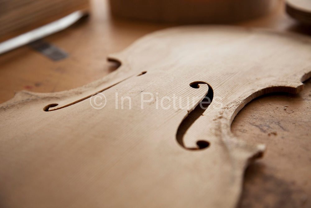 f-holes in the front. Violins being made at viloin an cello maker, Rod Ward's studio in Guilden Morden, Hertfordshire, UK. This highly skilled craft involves the process of making from raw wood to final instrument. All hand crafted with specialist tools and care for detail.