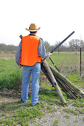 An aging man is dressed to hunt in denim and a blaze orange vest. Completing the ensemble is a straw cowboy hat, cowboy boots and a 12 gauge side by side double barrel shotgun. Wood and Steel fence posts are stacked together with the spares leaning against strands of barbed wire that complete the fence. This image available for EDITORIAL USE ONLY. A release may be required. Additional information by contacting alook at alanlook.com