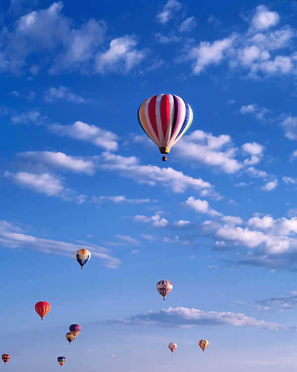 Brightly-colored hot-air balloons soar in the summer sky during a hot-air balloon festival in Teton Valley, Idaho.