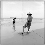 Two Vietnamese fishermen pull a net from the ocean filled with their daily catch, Danang, Vietnam, Southeast Asia