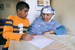 Boy helping his elderly grandmother fill out some forms as English is not her first language,